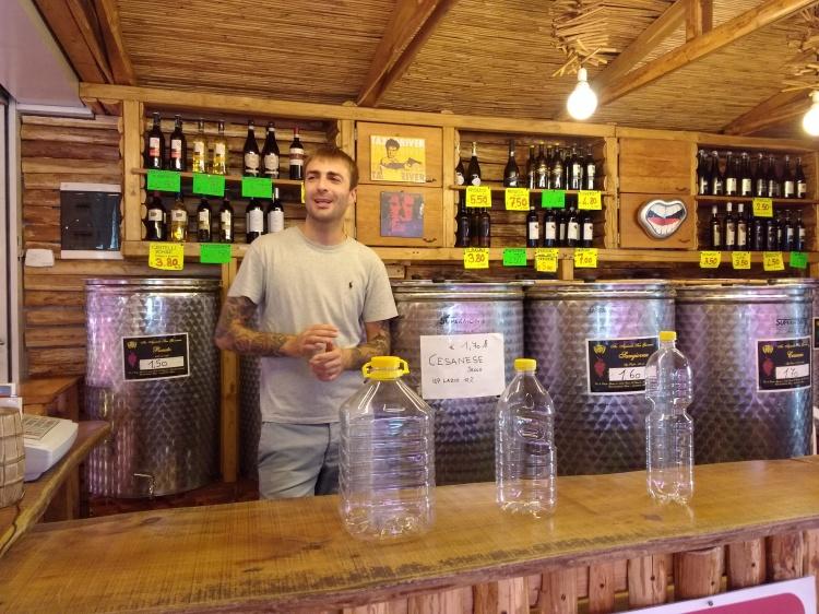 Manuele, el encargado de Vini Sfusi mostrándonos las cantidades de vino que suele vender por cinco euros o menos.